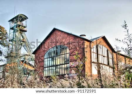 Old coal mine building with mining tower - stock photo
