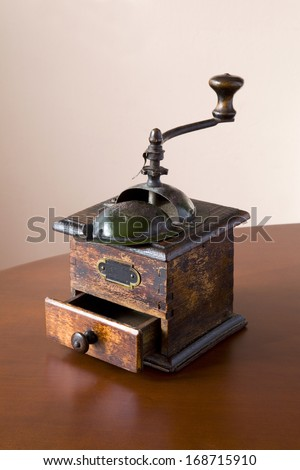 Old coffee grinder on a wooden table with open drawer. Old Coffee Grinder. - stock photo