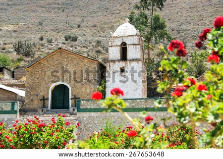 Old colonial church inside of the Colca Canyon in Peru with flowers in the foreground - stock photo