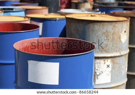 Old colored barrels for oil products. Empty rusted drums - stock photo