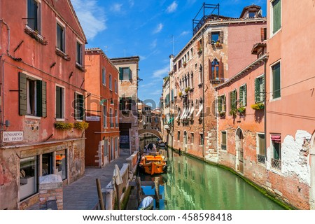 Old colorful houses and narrow canal between them under blue sky in Venice, Italy. - stock photo