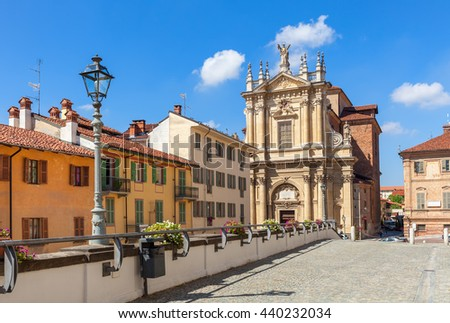 Old colorful houses, church and lampposts under blue sky in town of Bra in Piedmont, Northern Italy.