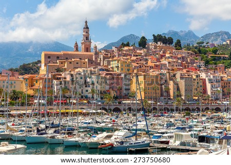 Old colorful houses overlooking small marina with yachts and boats in Menton - town on French Riviera. - stock photo