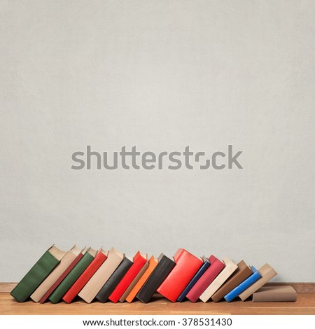 Old colorful leaning books on wooden floor near the white wall