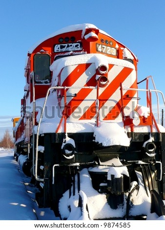 Old colorful red and white striped train outdoors in winter - stock photo