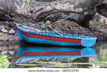 Old colorful row boat tied up to the shore on Lake Nicaragua, Granada, Nicaragua, 3 Mar 2016 - stock photo