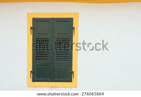 old colorful window with closed vintage wooden window shutters in a white exterior wall - stock photo