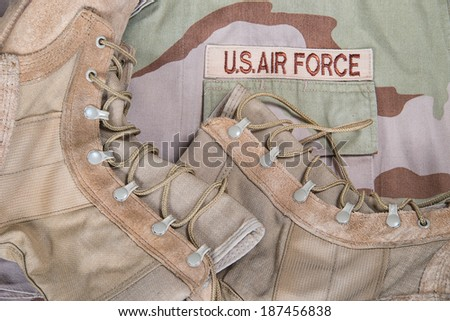 Old combat boots against Air Force camouflage desert uniform - stock photo