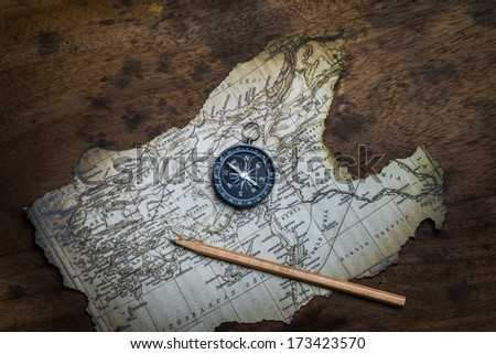 Old compass and and pencil on ancient map