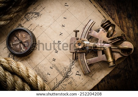 Old compass, astrolabe and rope on vintage map. Adventure stories background. - stock photo