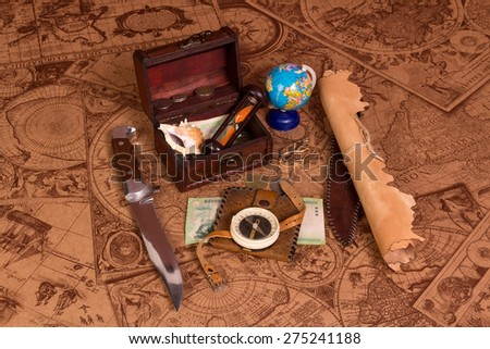 Old compass lying on antique map with treasure chest, knife, money,globe and starfishes - stock photo