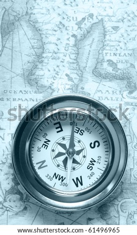 Old compass on ancient map. Blue toned image - stock photo