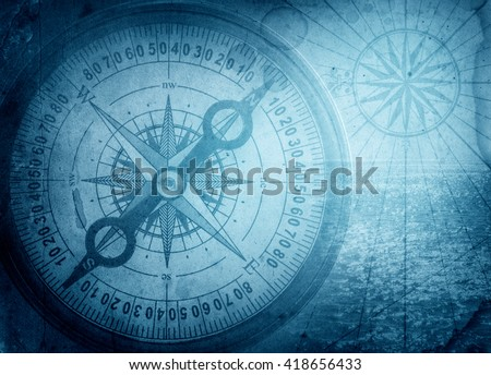 Old compass on vintage map. Pirate and nautical theme grunge background.