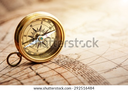 Old compass on vintage map. Retro stale. Shot with shallow depth of field. - stock photo