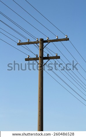 Old concrete electricity pylon in the countryside against the sky - stock photo