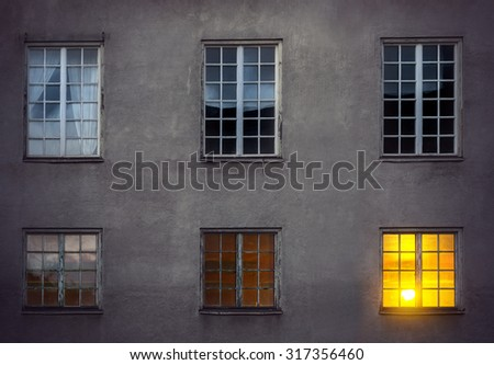 old concrete wall of industrial building with six windows at night