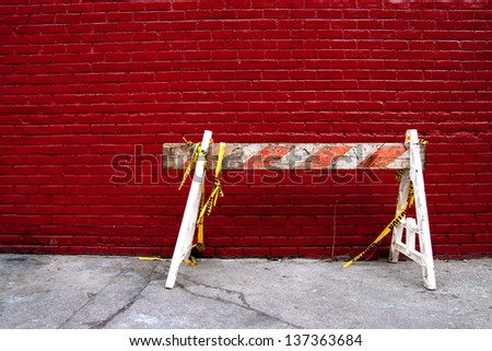 Old Construction Barrier Sawhorse on a sidewalk against a Red Brick Wall - stock photo