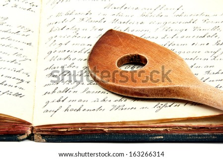 Old cooking book with wooden spoon - stock photo