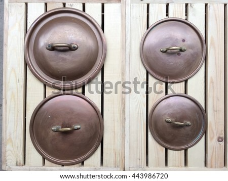 old copper lid on wood background - stock photo