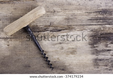 old corkscrew on the wood background - stock photo