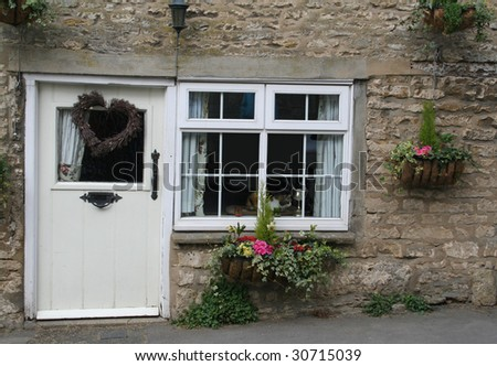 Old cottage in rural England with a cat looking through the window