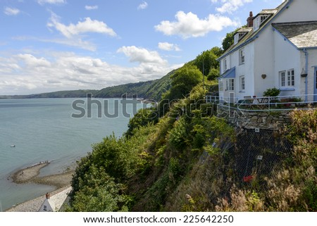 old cottage on a overhang at Clovelly, Devon view of old building in historic fishing village on Devon northern coast, shot in bright light  - stock photo