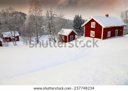 old cottages set in a snowy winter landscape, Sweden - stock photo