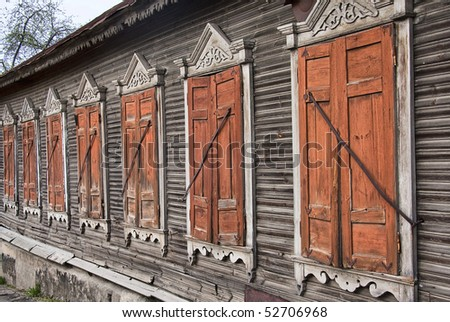 Old country house windows with closed shutters - stock photo