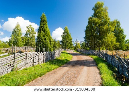 Old country road with old fashioned wooden fencing at roadside. Road moves through very fine landscape that is conserved and kept open. Fine summer day with sunshine. Smaland, Sweden.