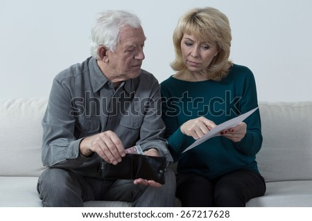 Old couple analyzing home budget and counting money - stock photo