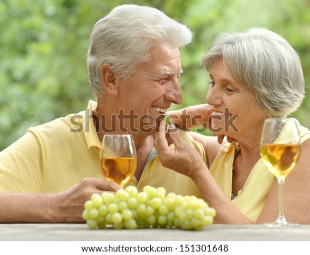 old couple drinking wine. Wife treats her husband grapes