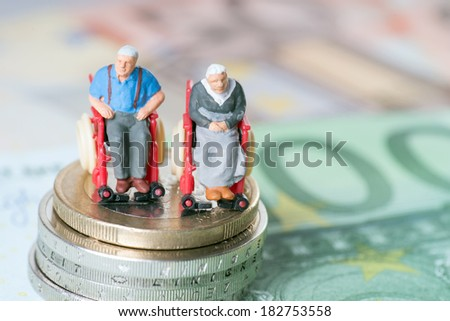 Old couple in a wheelchair with euro money / wheelchair users - stock photo