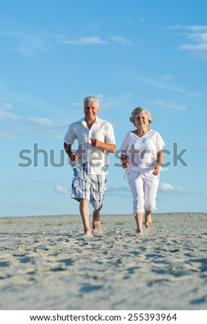 Old couple running on a beach in a sunny day - stock photo