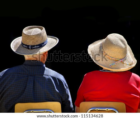 Old couple sitting in chairs wearing straw hats with black background - stock photo