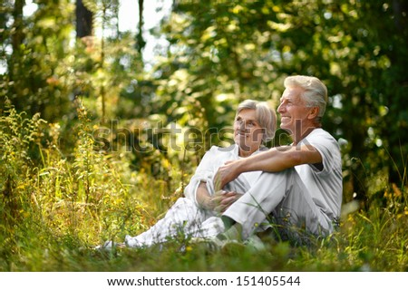 old couple sitting in grass in forest