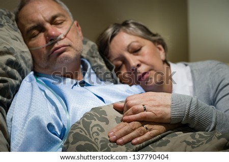 Old couple sleeping together in bed man with nasal cannula - stock photo