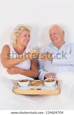 Old couple toasting at breakfast with orange juice and lying on the bed