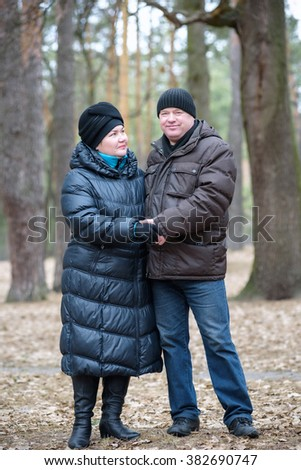 Old couple walking in the forest. Having a good time together. Smiling and talking together on autumn or spring forest.