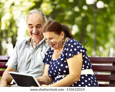 Old couple with tablet pc sit on bench  . Outdoor. - stock photo
