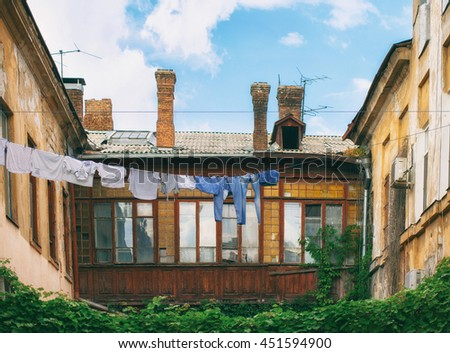 Old courtyard with hanging laundry. Picturesque courtyard - stock photo