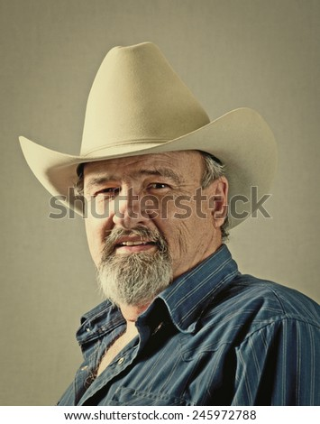 Old cowboy with a disdaining look. Retro instagram look.  - stock photo
