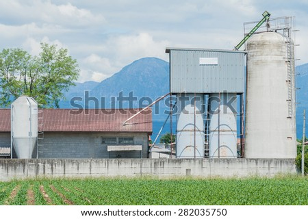 Old cowshed with old silos for cattle fodder - stock photo