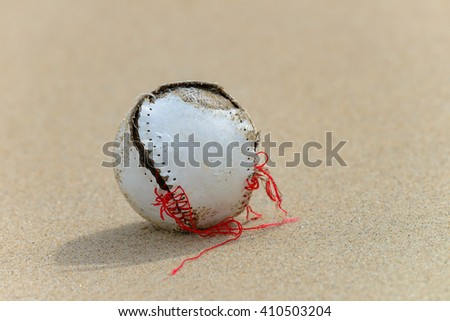 Old cracked baseball ball in sand - stock photo