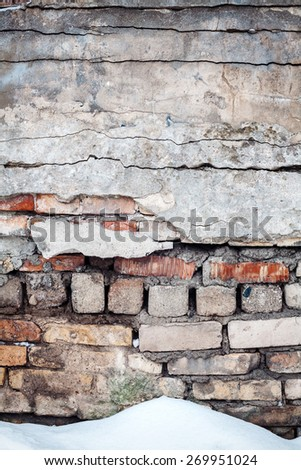 Old cracked wall of bricks and snow  - stock photo