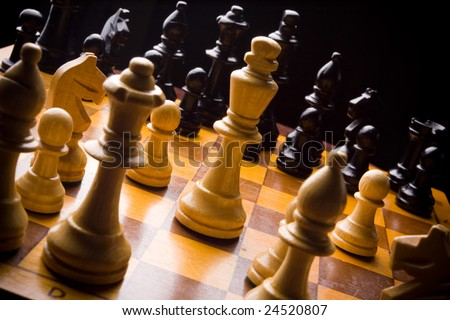 Old Craved wooden Chess pieces on a Board - stock photo