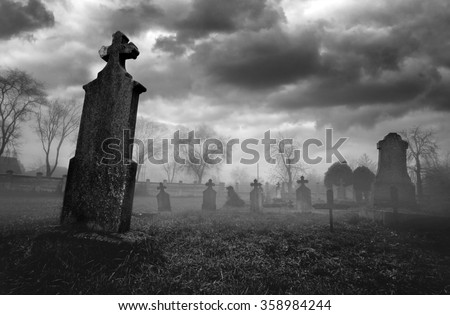 Old creepy graveyard on stormy winter day in black and white. - stock photo