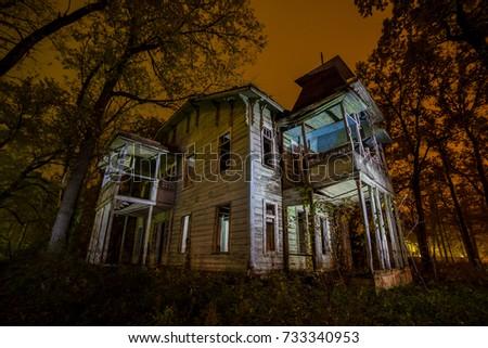 Old Creepy Wooden Abandoned Haunted Mansion At Night