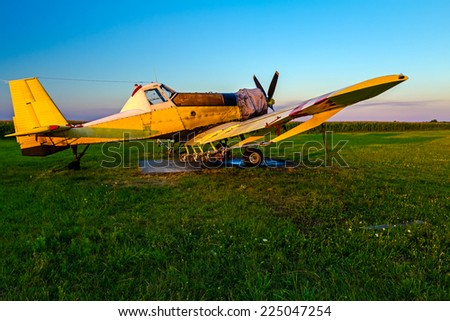 Old crop dusters lined up at airfield on green grass at sunset.  - stock photo