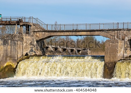 Old crumbling water gate of the abandoned hydroelectric power plant - stock photo