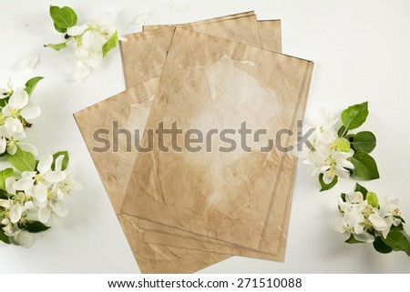 Old crumpled paper with white flowers white background - stock photo